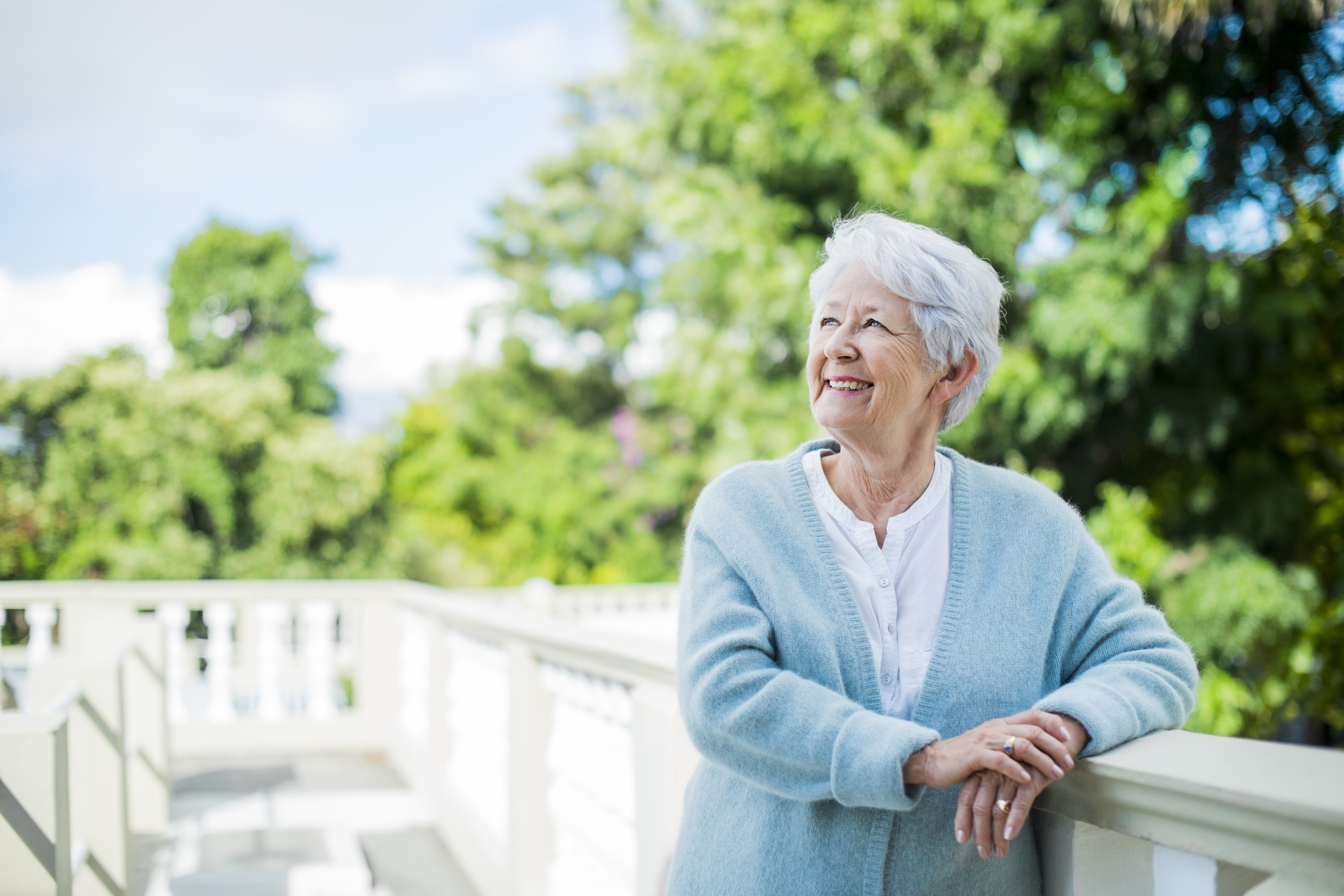 Happy thoughtful senior woman looking away while leaning on terrace railing