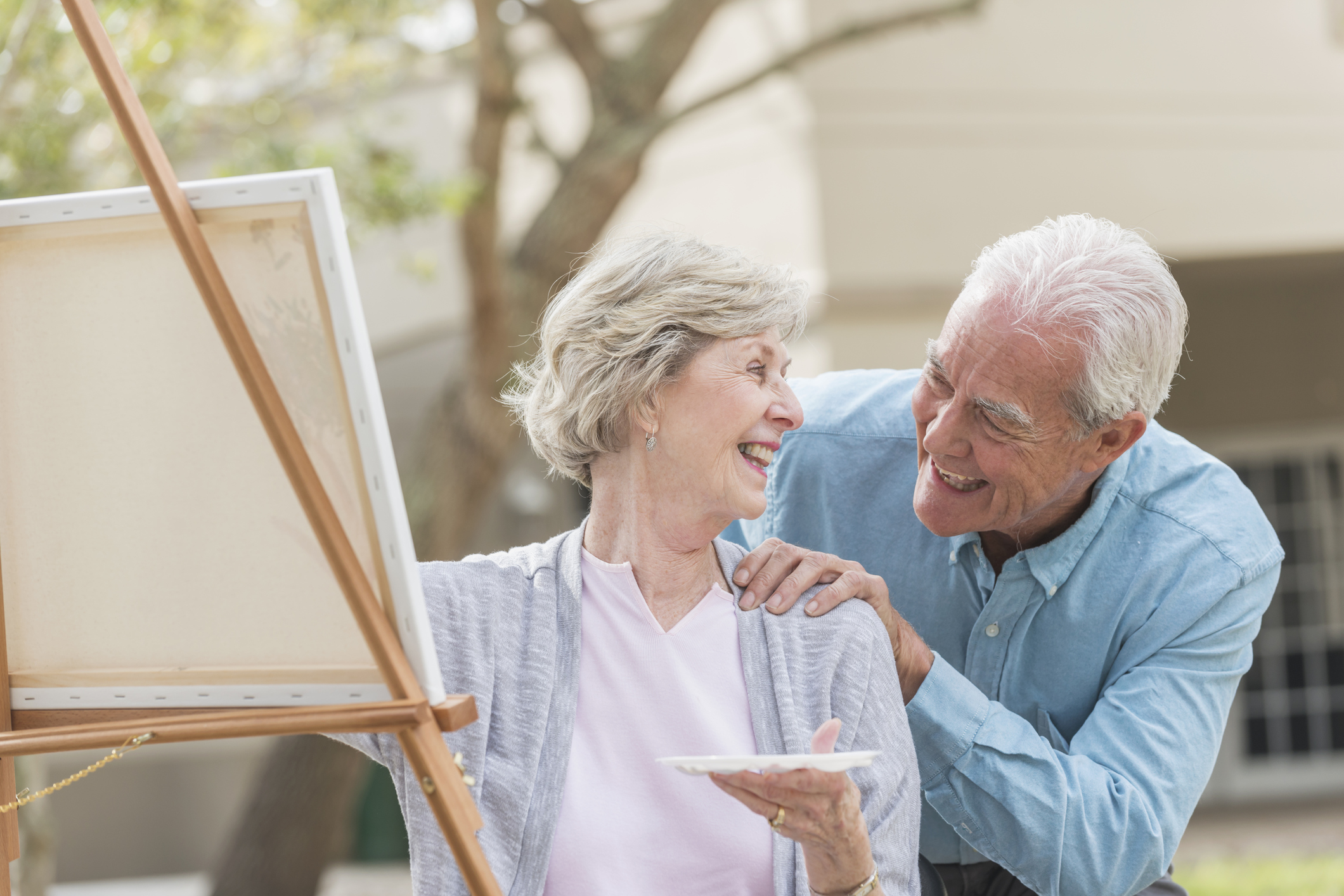 A senior woman sitting outdoors at an easel, painting a picture on canvas. She is turning her head to talk with her husband who is standing behind her with his hand on her shoulder. They are smiling.
