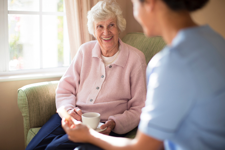Photo of nurse and elderly woman in pink sweater drinking tea on sofa in assisted living facility