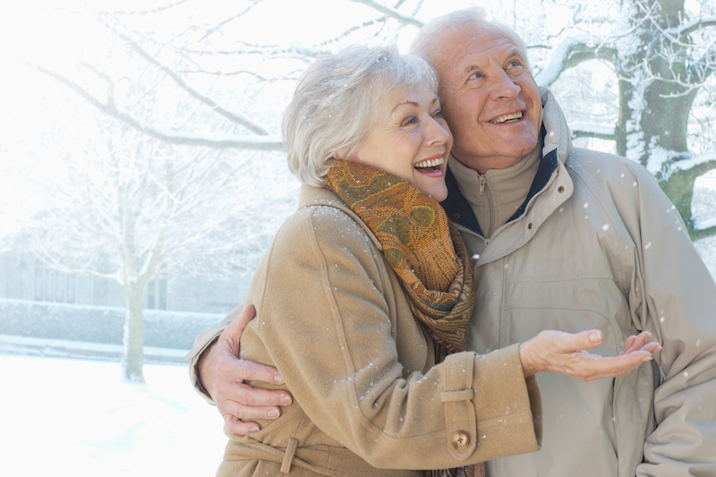 Older couple smiling in the snow outdoors