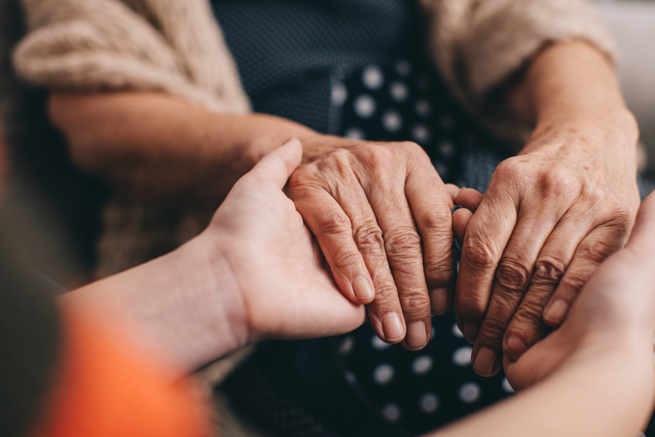 Hands of a young adult holding the hands of an older senior woman.