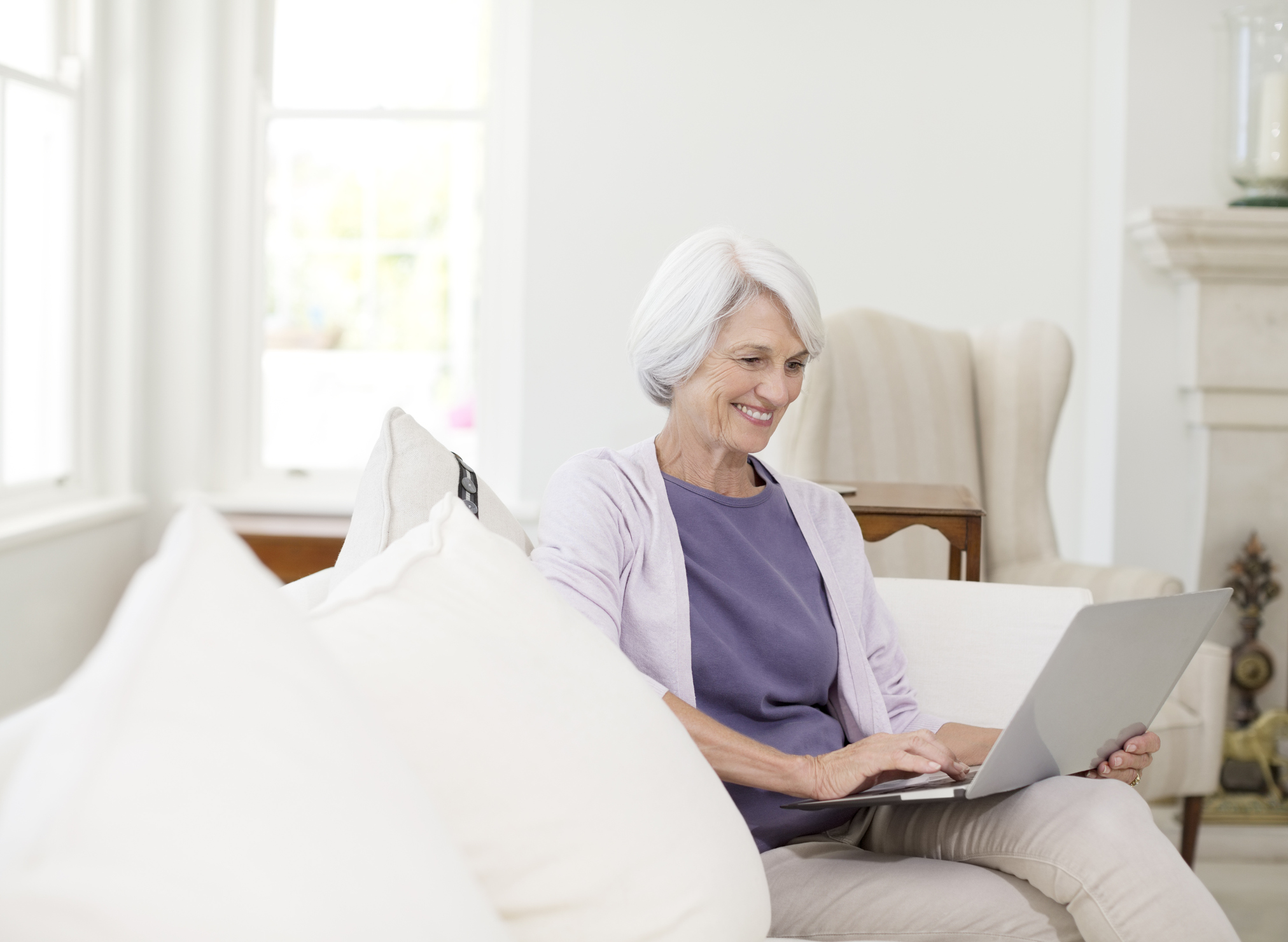 Senior woman using laptop on sofa in living room