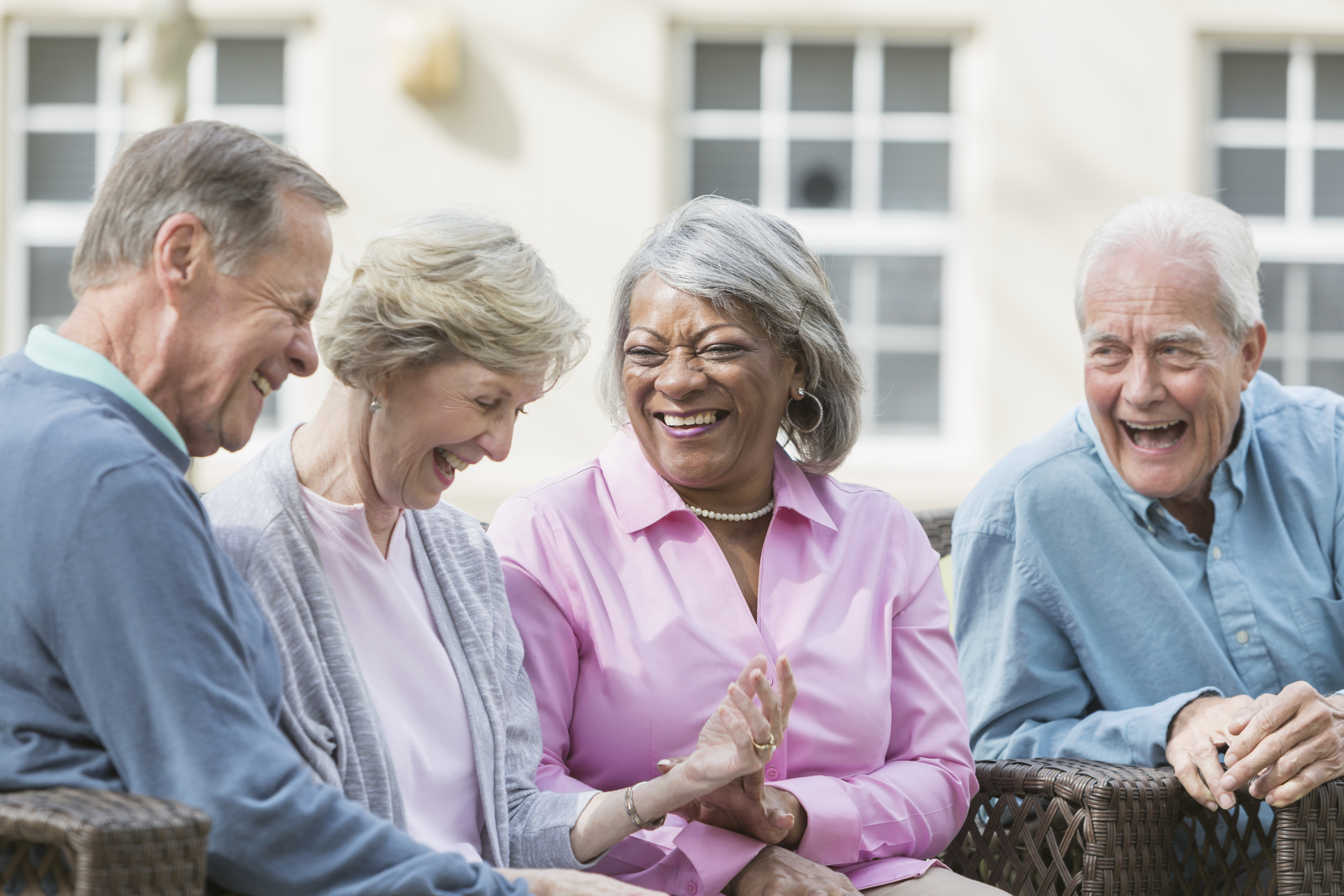 A group of four multi-ethnic seniors sitting together on patio furniture outdoors, talking and laughing. They are in retirement, relaxed and enjoying spending time with friends.