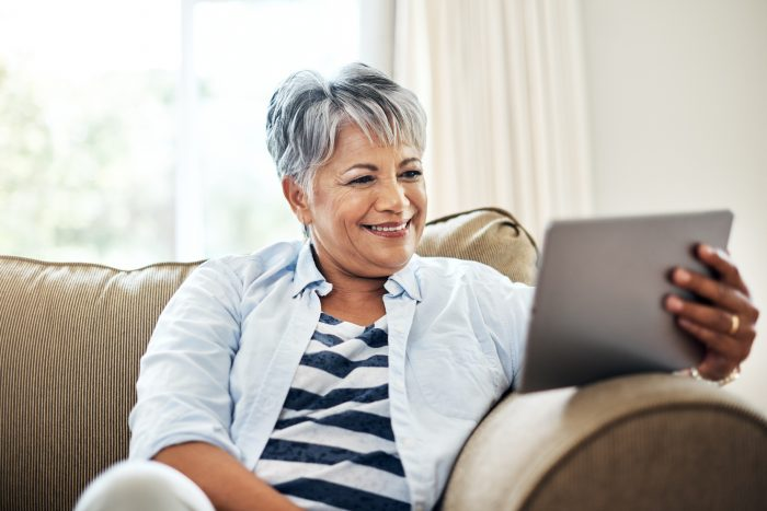Shot of a senior woman using a tablet at home