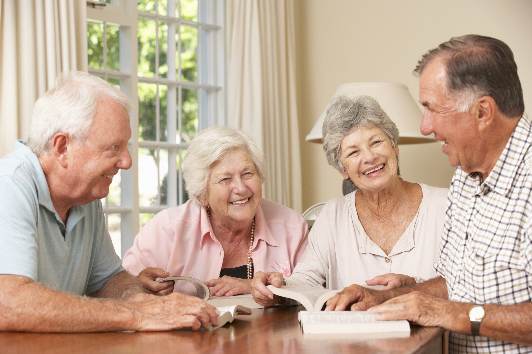Group Of Senior Couples Attending Book Reading Group Smiling And Laughing.